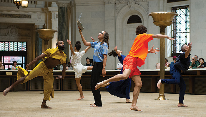 Five dancers encircle a sixth performer holding a laptop